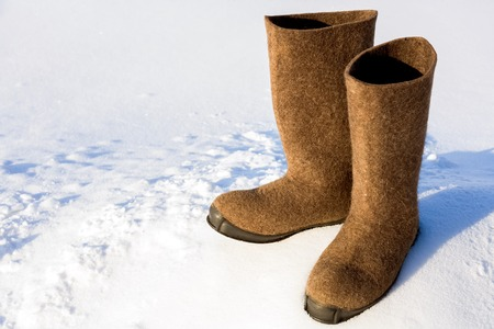 Warm Russian village felt boots of felt with a rubber sole are standing on a snow drift.