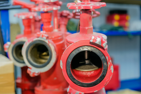 Three red fire hydrants with valves are in the warehouse. Close-up. Front view