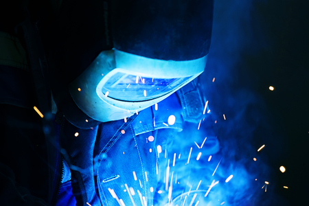 Welder helmet working in the shop. Bright sparks and smoke from metal welding.
