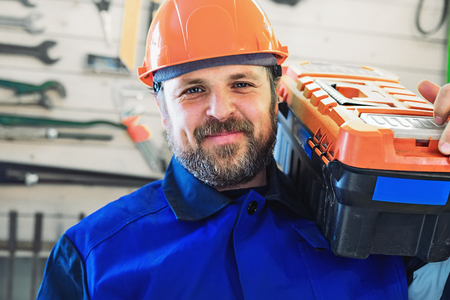 A worker in a helmet with a box of tools on his shoulder looks directly into the camera and smiles. Bearded man Caucasian appearance in work clothes on the background of the wall with tools.