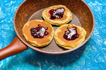 Three pancake in a frying pan, doused in raspberry jam. Baking sweet and delicious dessert ready to eat