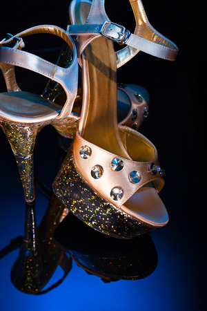 High-heeled shoes with precious stones and rhinestones. Shoes for Striptease and private dances. Close-up on glass surface with reflection