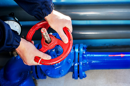 The hands of the worker Unscrew rotate the red valve to supply the gas supply.