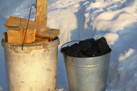 Two buckets filled with coal and wood are standing on the snow. Preparing for the heating season in the village. Banque d'images