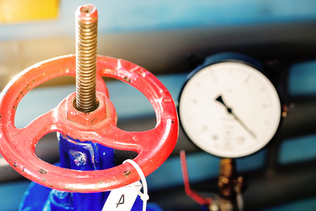 Red gas valve and pressure gauge with an arrow on the limit. Background for gasification. Close up. Stock Photo