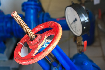 red valve and pressure sensor on the gas supply or heating pipe. Industrial background with close-up of aggregates and devices.