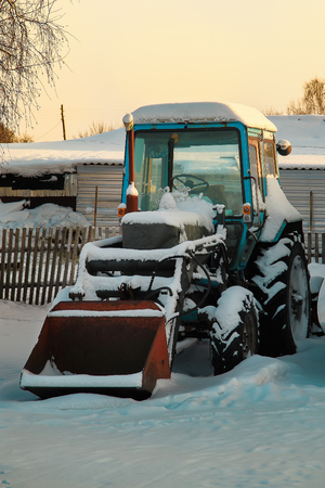A tractor with a spade stands covered with snow on a farm. Farmer machinery is standing outdoors. 免版税图像