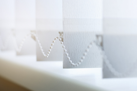 A row of white vertical blinds  cover the sunlight from the window. Close-up with copy space