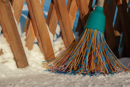 A plastic broom with multicolored bristles of the pile stands in the snow.