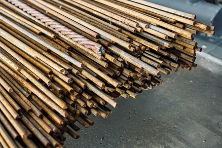 Metal rods lie in a pile on a concrete floor in the production hall.