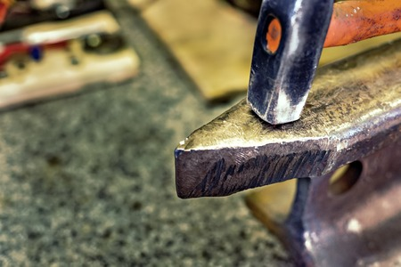Hammer on a metal anvil in a workshop. Close-up of metalworking tools.