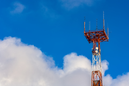 Tower connection with the mast and antennas against the blue sky with clouds. Transmission and reception of signals. Copy space.