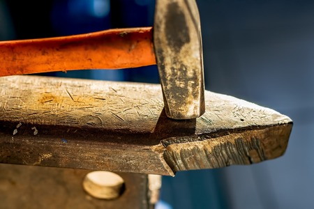 Hammer on a metal anvil in a workshop. Close-up of metalworking tool in daylight.