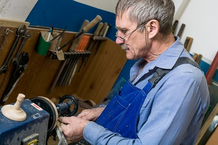 A white elderly man with glasses works at a lathe in a carpentry workshop. The concept of increasing the retirement age