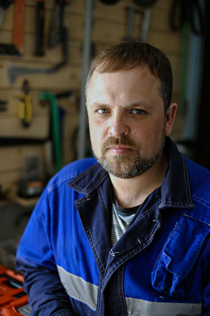 Portrait of a locksmith in overalls against the background of tools. White male at work looking into the camera