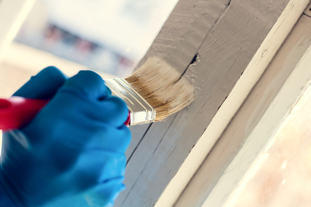 A gloved hand paints a window frame. Repair in the house. Services painter.
