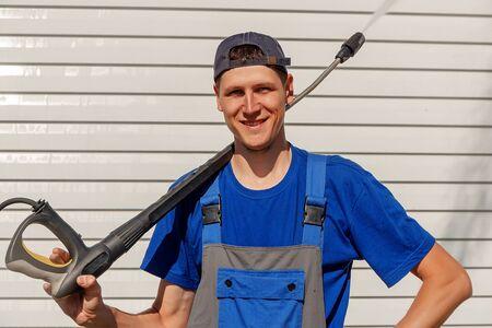 Servicio de limpieza del trabajador con una gorra de béisbol y un mono. Lavado de casas y fachadas Foto de archivo