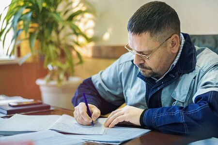 A male engineer in glasses in the office at the table signs the documents. Inspection, recording of prescriptions and violations in the log. Stock fotó