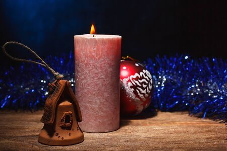 A burning candle and Christmas toys with tinsel stand on a wooden surface. Preparation and meeting of the Christmas holidays and vacations.