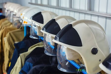 Rescue clothing hanging on hangers. Many helmets of firefighters in a row. Фото со стока
