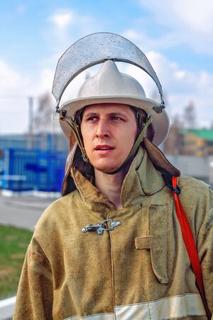A fireman in protective clothing and a helmet looks to the side. Portrait of a white young male lifeguard outdoors with natural light. After performing rescue and extinguishing.