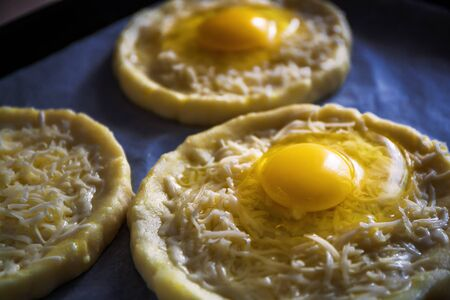Khachapuri from rice flour, cottage cheese dough with egg and mozzarella cheese. Preparation for baking. View from above.