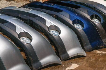 Many car front bumpers are folded in a row. Parsing. Auto repair shop.