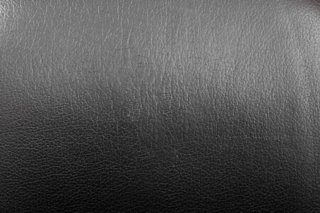 The texture of black leather close-up. Transition from light to shadow. Empty surface abstract background for design.