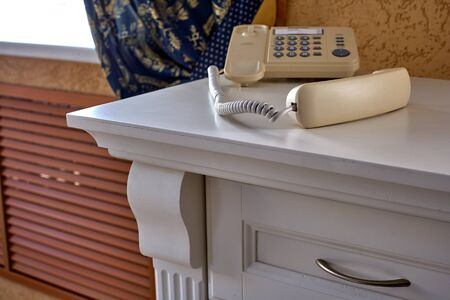 The handset of a push-button phone lies on a white vintage table. The concept of a call center, support service, or negotiation