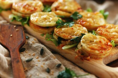 Sandwiches from zucchini with herbs lie in a row on a wooden board. Rustic still life of a simple snack.