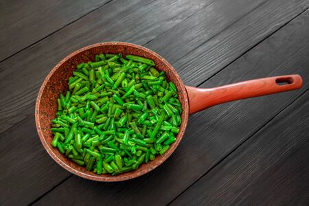 Cooked green beans in a frying pan on a black wooden background. Space to copy. Top view