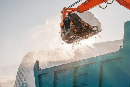 Snow removal after snowfall and blizzards. Excavator loads snow into a truck