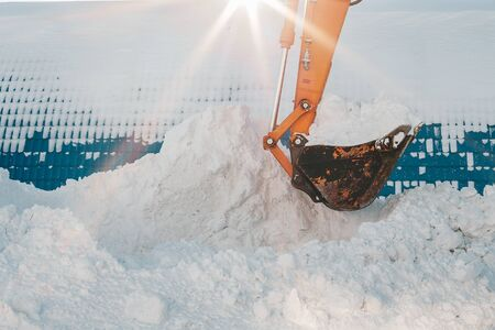 Snow removal after snowfall and blizzards. Excavator loads snow into a truck. The work of utility services during the winter of period