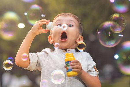 A child with an open mouth and big eyes blows colorful soap bubbles in nature