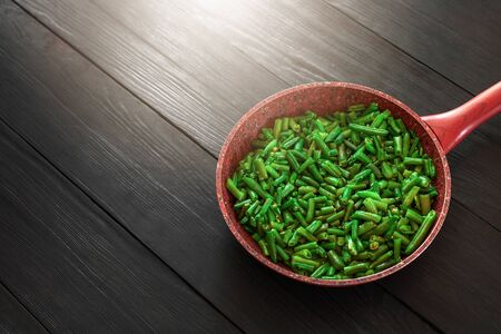Pod beans in a frying pan with sunlight. A recipe for healthy eating.