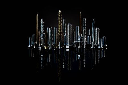 The city at night from small screws and bolts. Advertising photo of materials and products for construction.Many shiny screws of different lengths on a black background..