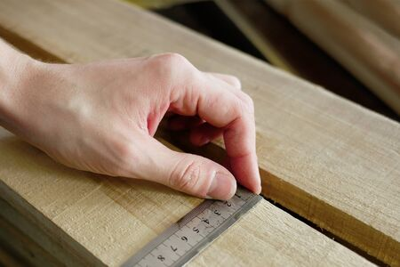 Construction and repair. Men's hands line measure the width of a wooden board. Hands with a close-up tool. Production control. Banque d'images