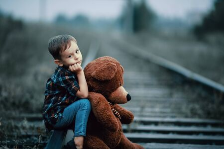 An abandoned homeless child, an orphan. A lonely boy hugs a stuffed toy and sits on the tracks, looking sadly at the camera. Street children from dysfunctional families.