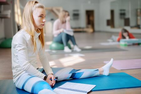 A beautiful blonde with loose hair sits in a fitness Studio and attentively listens to the master class. Training in Pilates or yoga. Copy space
