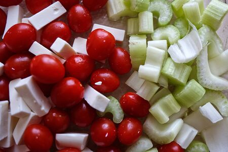 A simple salad for a healthy diet. Cherry tomatoes, celery and slices of cheese. Fresh vegetables for a vitamin diet.. Top view.