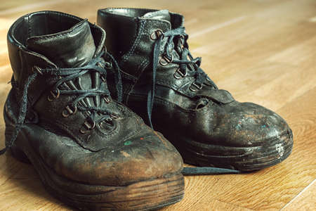 Old worn work boots with lacing. Leather shoes that require repair or replacement. Closeup 写真素材
