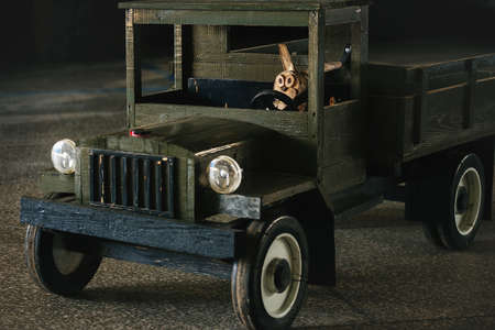 Alert and attentive driver behind the wheel of a wooden truck. Concept of traffic rules