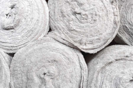 White non-woven fabric in rolls is on the shelves of the warehouse. Covering material. Textiles for the production of rags. Close-up with copy space Stock Photo