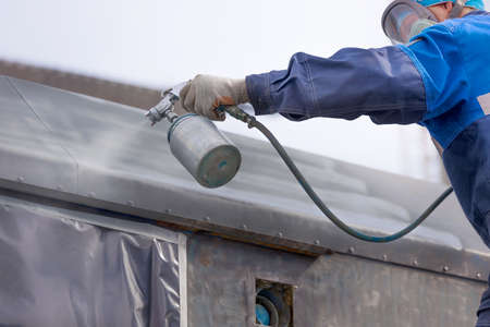 Industrial work. Priming of metal products from the compressor gun. A worker in overalls and a protective mask paints the body of a truck trailer or a metal car.