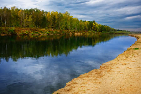 Calm picturesque landscape of Russian nature. The river flows between the sandy shore and the forest. Reflection of the sky in the water. 免版税图像