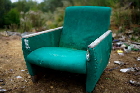 The old chair is in a landfill. Abandoned wasteland with waste and garbage. A symbol of former greatness