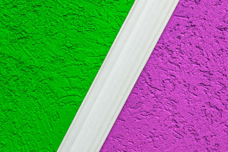 Rough plaster surface painted in a bright color. Variations of harmony and color compatibility in the repair. A sample of paint mixing on the wall with space for copying. Abstract background for the design.
