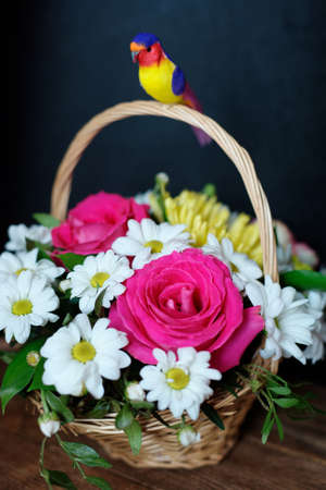 Gift bouquet of flowers in a wicker basket with a handle on a dark background. Flower arrangement for greeting close-up