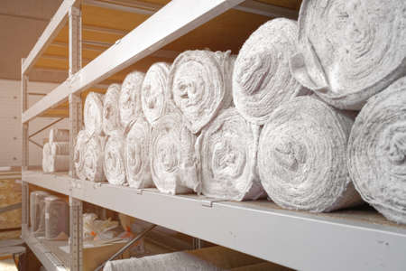 White non-woven fabric in rolls is on the shelves of the warehouse. Covering material. Textiles for the production of rags. Close-up with copy space