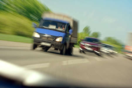Truck in a blur on the road in motion. The danger of a collision or emergency situation. Violation of rules by truckers. The concept of vigilance at the wheel 免版税图像 - 159312823